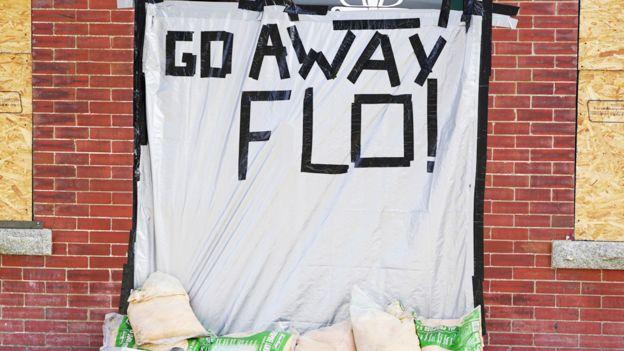 """Plástico con un cartel que dice """"Vete Florence"""", en un casa con las ventanas tapadas con paneles de madera compensada"""