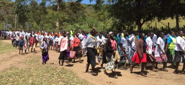 Parents and students form a long line as they walk along a dirt track for their anti-FGM march