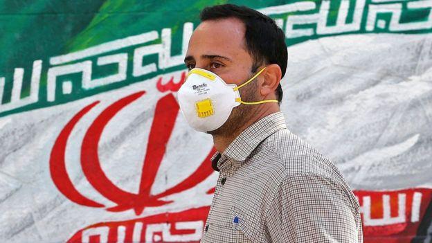 Иранский мужчина в маске на фоне национального флага