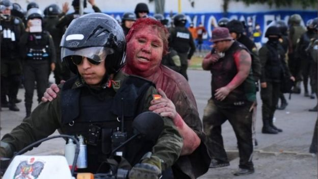 Police took Vinto mayor Patricia Arce Guzman away on a motorcycle after people threw paint at her