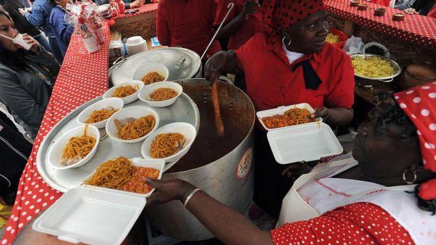 Dos mujeres negras sirven platos en la feria gastronómica mistura
