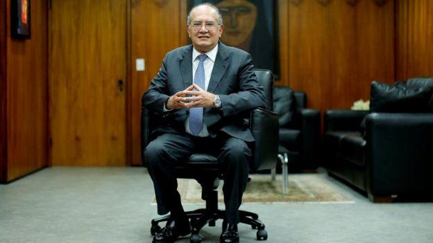 Gilmar Mendes aparece sentado dentro de escritório