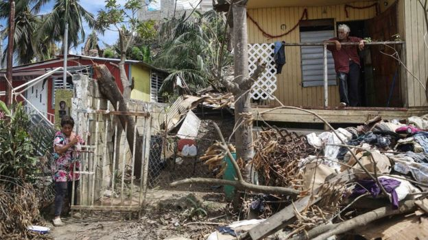 Two residents of San Isidro, Puerto Rico stood outside their damaged house after Hurricane Maria struck the island.