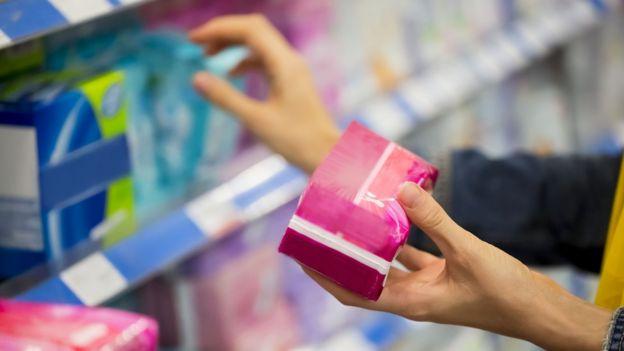 Una mujer comprando toallas higiénicas.
