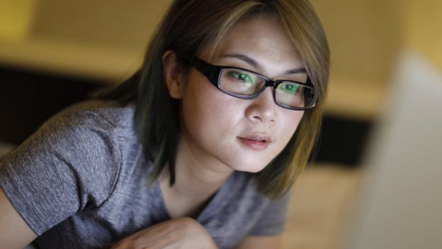 Una joven china mirando una pantalla.