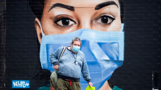 Man in a mask walks past a mural of an NHS worker in a mask, London