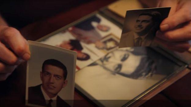Jack Zawadski holds photos of his husband Robert Huskey