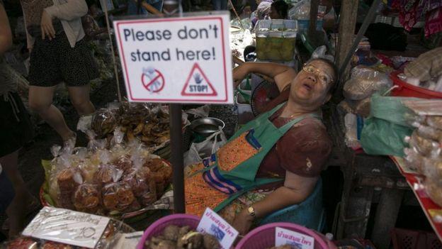 إحدى البائعات في سوق مايكلونغ بتايلاند محاطة بالسياح