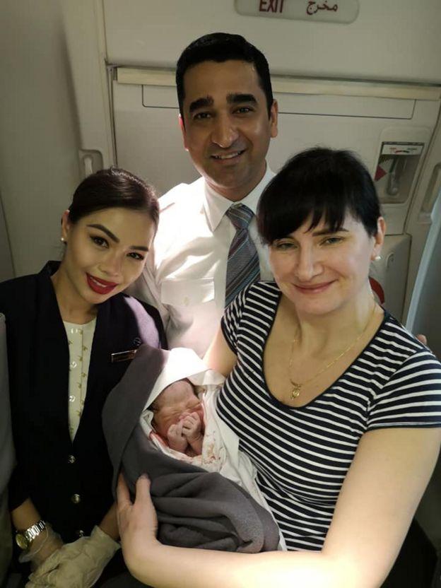 Алена Федченко и члены экипажа с ребенком, родившимся на борту самолета Qatar Airways