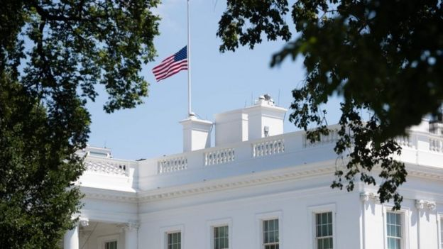 The American flag flies at half staff over the White House in Washington, DC, July 18, 2020