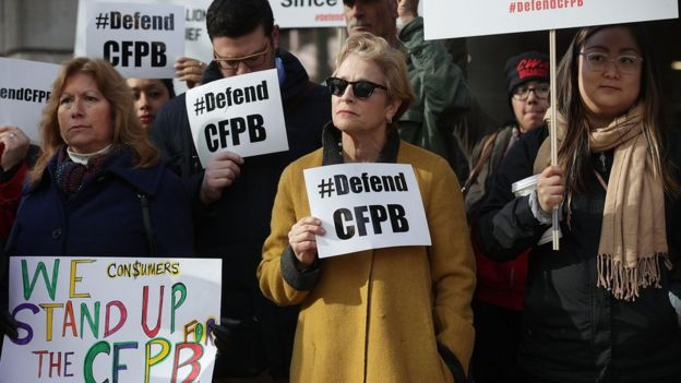 Supporters of the Consumer Financial Protection Bureau hold signs as they gather in front of the agency in Washington DC