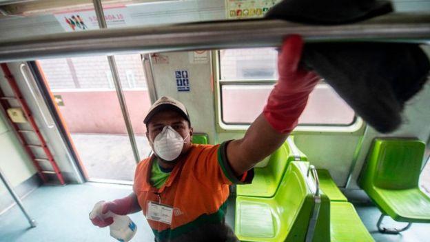 Hombre limpia el interior de un bus en México