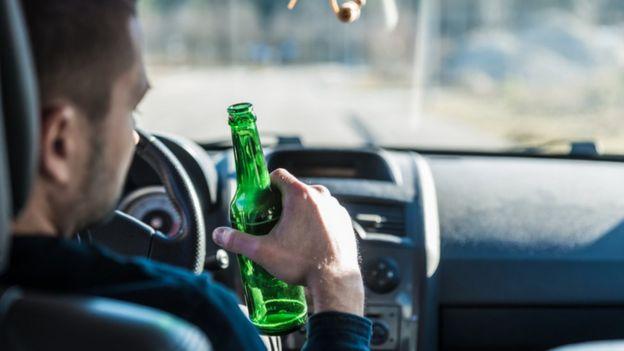Hombre manejando con una cerveza en la mano.