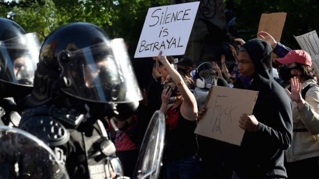 Manifestantes com cartazes protestam em frente a grupo de policiais com armas e equipamentos anti-manifestação