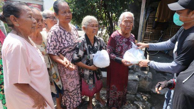 Warga antre untuk mendapatkan bantuan sembako di Kelurahan Pojok, Kota Kediri, Jawa Timur, Selasa (07/04).