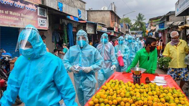Medical staff wearing Personal Protective Equipment (PPE) gear walk through a market for a door-to-door screening inside a Mumbai slum