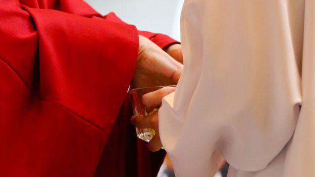 Sacerdote lavando mãos em uma missa