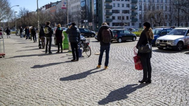 People line up in front of an organic grocery store in Berlin, Germany, 24 March 2020
