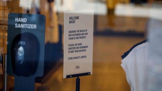 Uma placa dando as boas-vindas aos clientes é vista ao lado de uma estação de desinfetante para as mãos dentro de uma loja Zara fechada