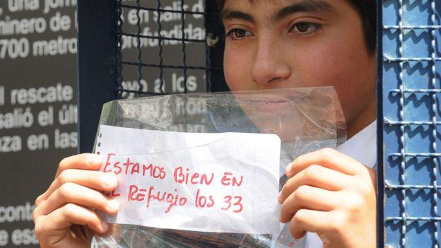 """Estudiante con el mensaje """"Estamos vivos los 33 en el refugio""""."""
