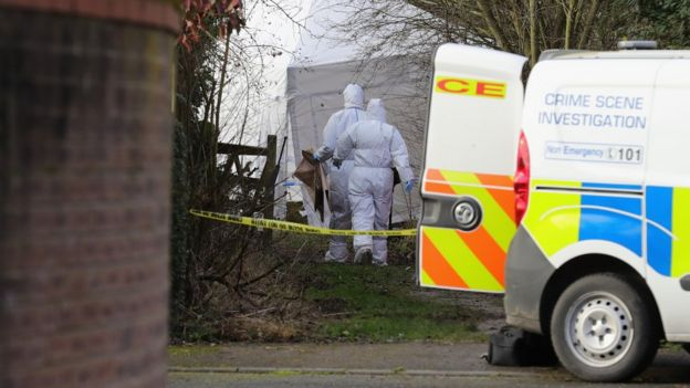 Police scientific officers work at a crime scene in Alness Drive