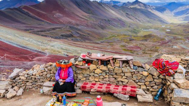 Mujer andina sentada de espaldas a la Montaña de los Siete Colores.