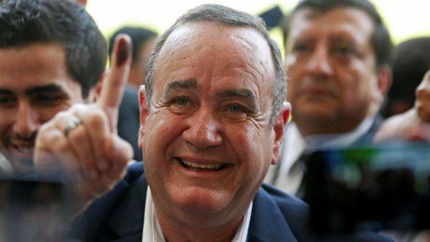 8月11日,Alejandro Giammatei在危地马拉城的一个投票站投票后,展示了他墨水般的手指