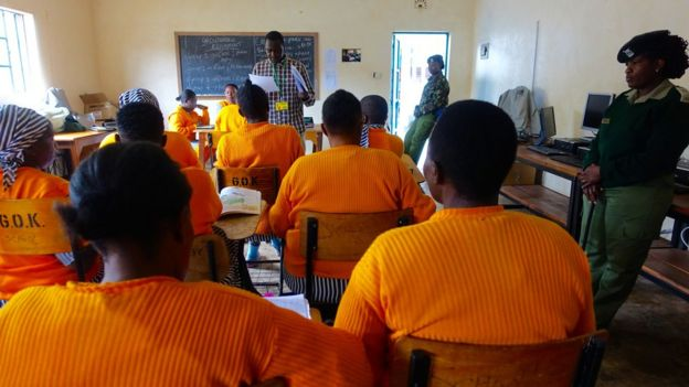 Inmates wearing orange and listening to a teacher in a classroom