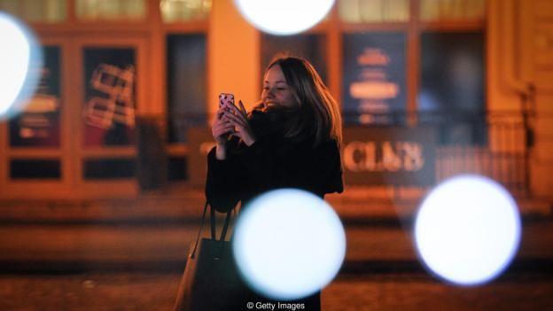 Una mujer con su móvil en la calle.