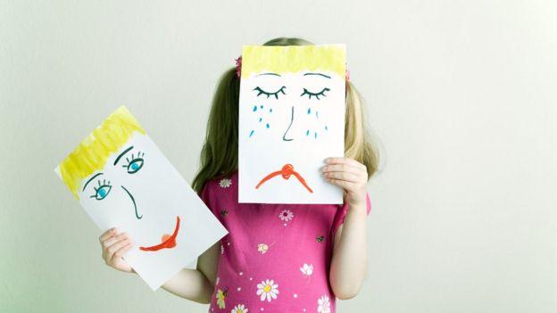Criança segura desenhos simbolizando tristeza e alegria