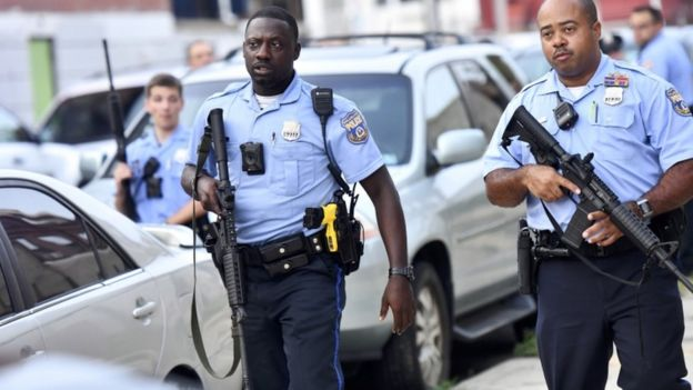 Police officers hold guns near the scene of a shooting in Philadelphia