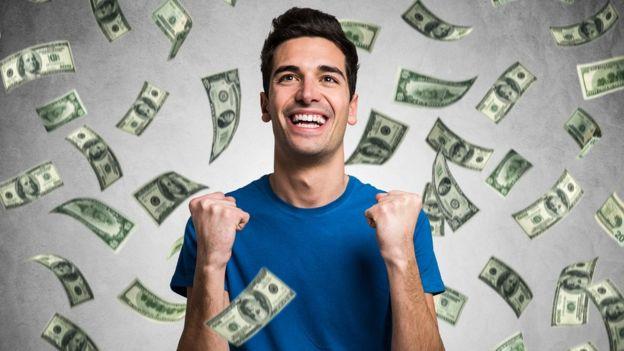 Hombre joven feliz con lluvia de dólares.