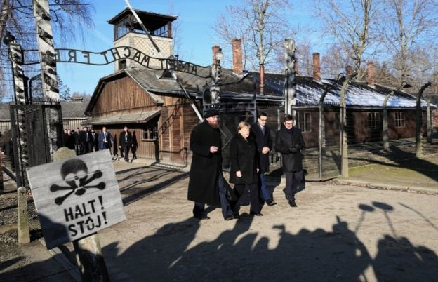 German Chancellor Angela Merkel walks through the gates of the Auschwitz-Birkenau Memorial and Museum, accompanied by Polish Prime Minister Mateusz Morawiecki