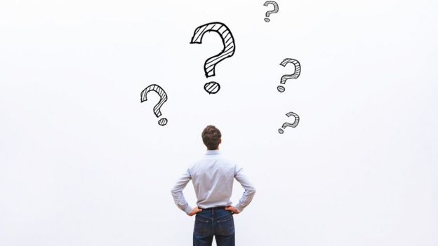 Hombre observa un pared con signos de pregunta.