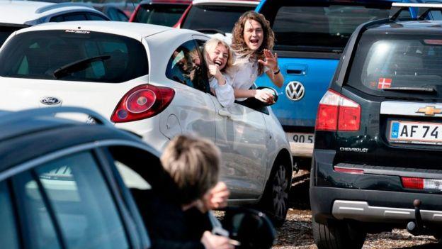 Daneses festejan la Pascua desde sus carros en un aparcamiento.