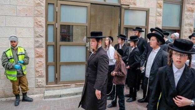 Ultraortodoxos tratan de entrar en una sinagoga después de que la policía ordenó que salieran.