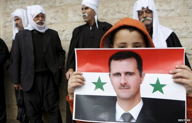 A Druze boy holds up a poster of Syrian President Bashar al-Assad in the village of Buqata, in the Israeli-occupied Golan Heights (17 April 2013)