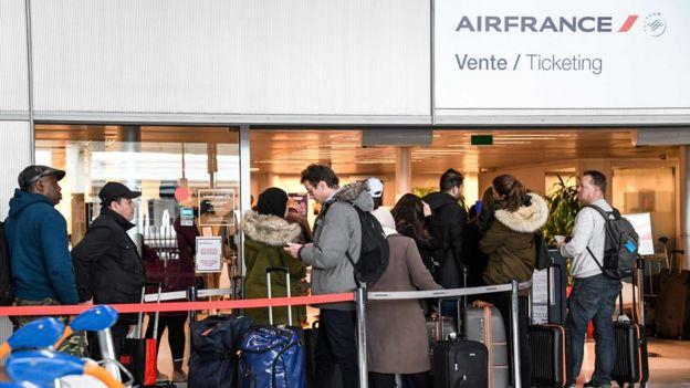 Grupo de pessoas em aeroporto da França