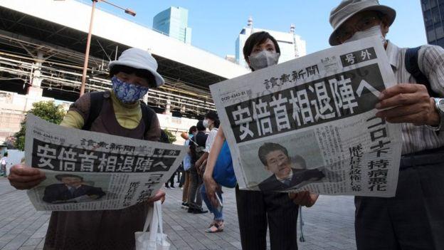 Japoneses eleyendo en prensa sobre la renuncia de su primer ministro.