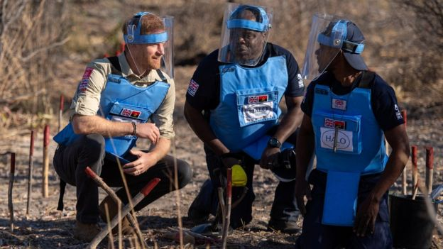 Prince Harry crouches alongside Halo staff