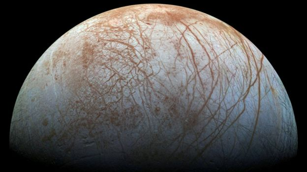 An ice moon with red streaks and patterns across its surface