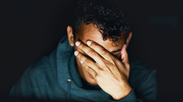 Hombre joven con mano cubriéndose la cara en señal de preocupación.