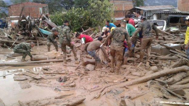 Soldados e voluntários em área de deslizamento resgate