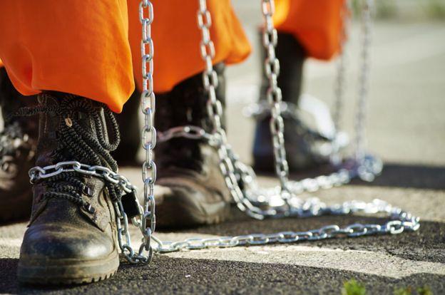 Prisioneros con cadenas en los pies.