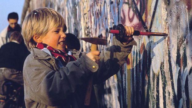 طفل يحاول هدم جدار برلين