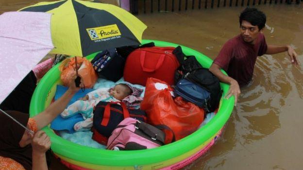 Um bebê é evacuado por uma equipe de resgate