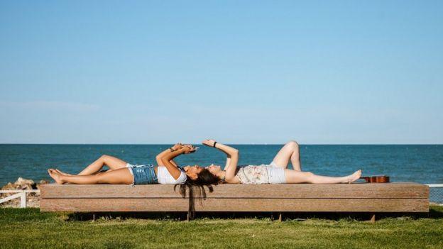 Des filles allongées sur un banc, au bord de la mer, en train d'envoyer des textos.