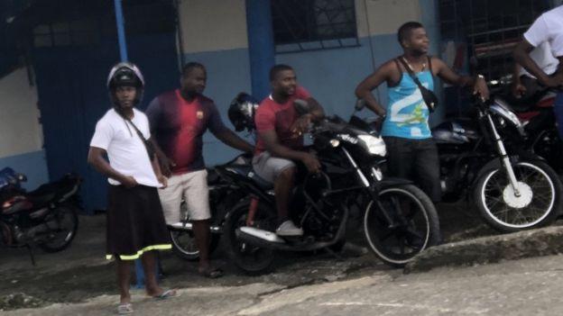 Un grupo de motoratones observa desde el lado de una calle en Buenaventura