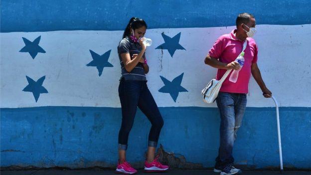Hondureños ante la bandera nacional.