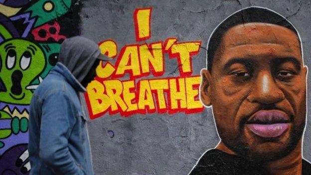 Homem passa por um grafite em uma parede representando um retrato de George Floyd no distrito de Prenzlauer Berg, em Berlim, em 30 de maio de 2020.